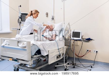 This will help. Prominent caring young woman suggesting old lady not taking off her oxygen mask until she recovering fully