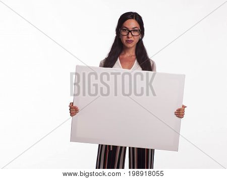 Young confident woman portrait of a businesswoman showing presentation, pointing placard gray background. Ideal for banners, registration forms, presentation, landings, presenting concept.