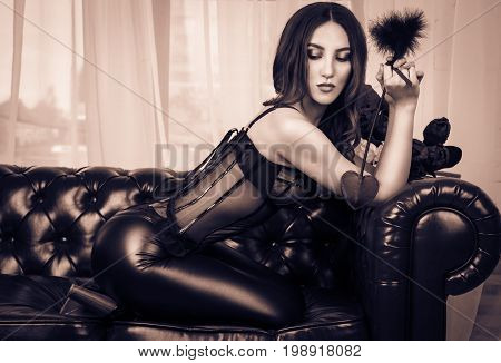 A sexy woman in leather pants and a corset erotically sits on the couch. Sensual girl in leather clothes posing on leather sofa. Vintage tinting