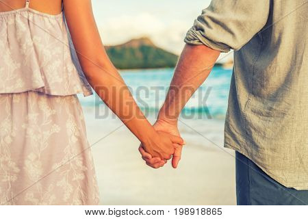 Couple holding hands relaxing on Hawaii beach in sunset. Young people in love in Waikiki travel Honolulu, Hawaii.