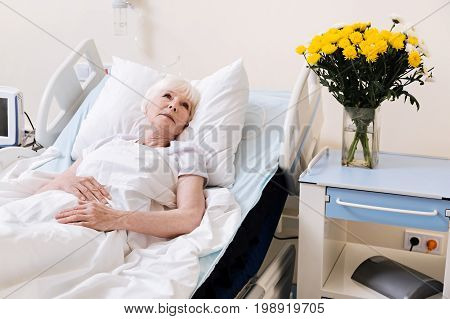 Dreaming of home. Feeble pale aged woman resting in hospital bed and getting better while nice bouquet from her family standing on a table