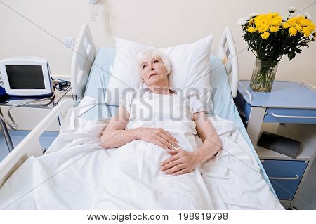 Looking forward to future. Sick weak old lady seeming feeble while lying in bed and slowly recovering from her illness