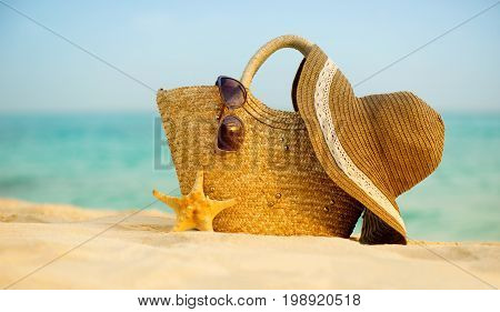 Bag of hat and glasses on the beach