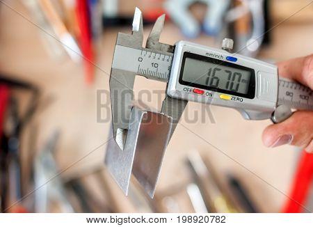 man measuting metal part with calipers in workshop