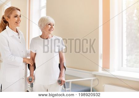 Still using crutches. Bright energetic elderly woman going through a rehabilitation while recovering from the injury and following doctors instructions