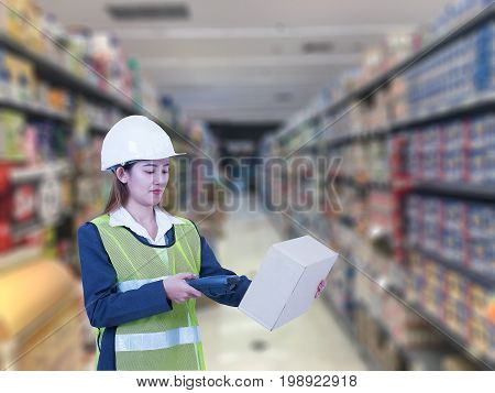 Postwoman worker scanning package with barcode scanner in warehouse for delivery.