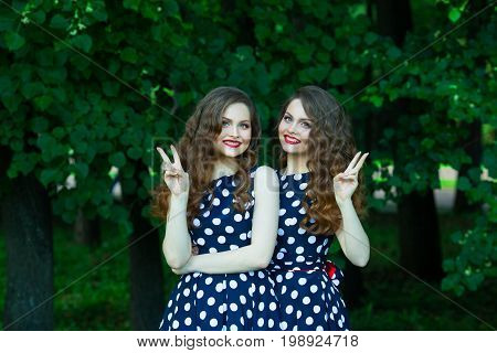 Two beautiful smiling girl sisters twins for a walk in summer park on a background of greenery with makeup and hairstyle