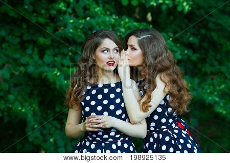Two beautiful sisters twin girls on a walk in summer park on a background of greenery with makeup and hairstyle
