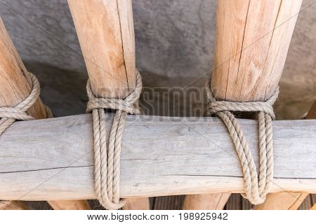 Rope tied around a wooden fence pole