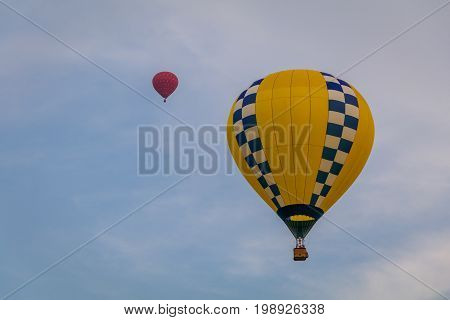 Yellow and blue patterned hot air balloon floats through the sky at dusk at Warren County Farmer's Fair on 8/1/17