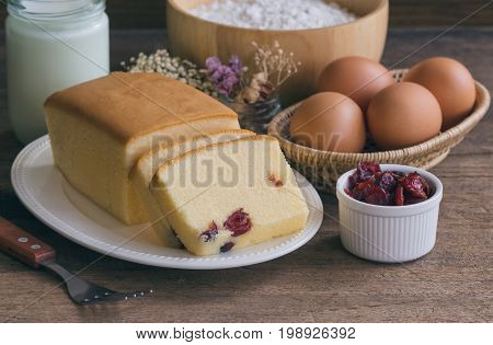 Slices of butter cake on white plate. Homemade butter cake with dried cranberries so delicious soft and moist. Tasty pound cake or butter cake ready to served on rustic wood table. Homemade bakery concept for background or wall paper.