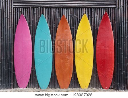 Colored surfboards leaning up against a wooden fence on beach
