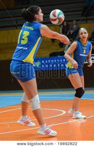 KAPOSVAR, HUNGARY - DECEMBER 19: Gabriella Kondor (L) receives the ball at the Hungarian NB I. League woman volleyball game Kaposvar vs Palota Bollhoff on December 19, 2010 in Kaposvar, Hungary.