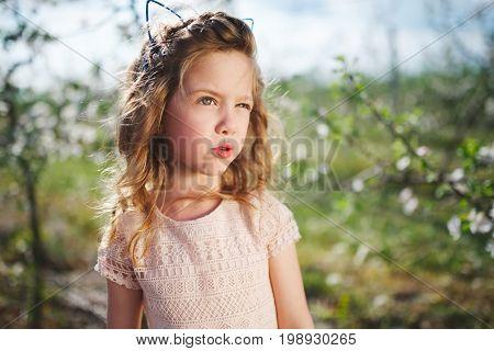 cute beautiful little girl in blooming garden
