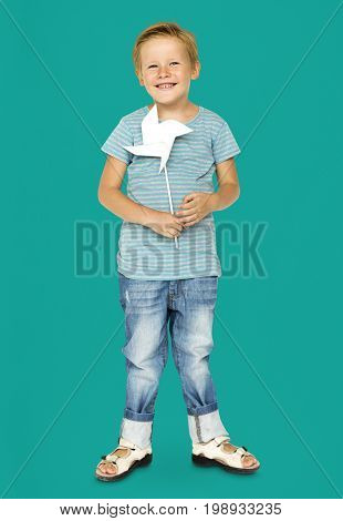 Happiness little boy smiling and holding pinwheel studio portrait