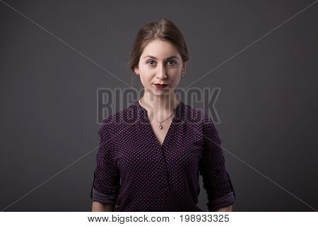 Stylish young businesswoman with a friendly expression looking directly at the camera, closeup of her face on a grey background