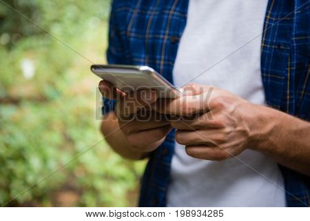 Mid-section of man using mobile phone in garden