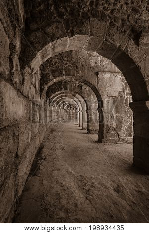 Internal passages in the ancient Roman amphitheater of Aspendos. The province of Antalya. Mediterranean coast of Turkey. Sepia. Toning. Stylization.