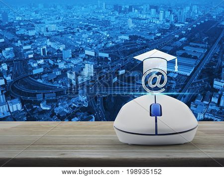 e-learning icon with wireless computer mouse on wooden table over city tower street and expressway Study online concept