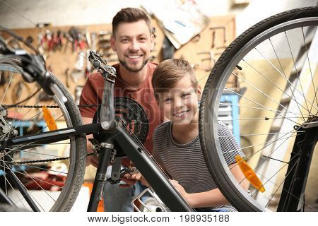 Dad and son fixing bicycle in garage