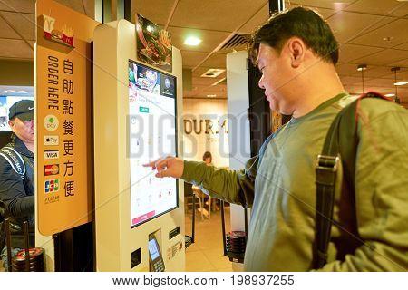 HONG KONG - CIRCA NOVEMBER, 2016: a man use a Mcdonald's ordering kiosks in Hong Kong. McDonald's is an American hamburger and fast food restaurant chain.