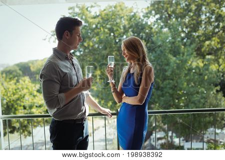 Couple interacting with each other while having champagne in restaurant