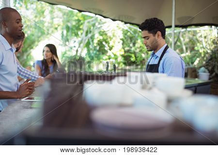 Male waiter taking order at counter in outdoor cafe