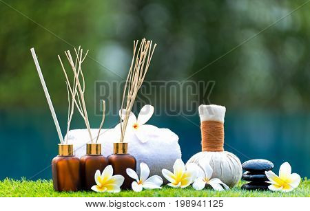 Spa treatment and product for hand and foot spa with flowers and water soft focus; Spa herbal compressing ball white frangipani flowers Thailand. Greenery tone 2017