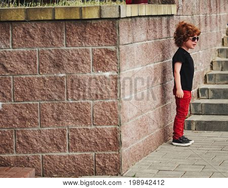 little crying boy with red hair outdoors
