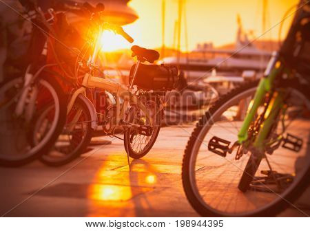Parking for bicycles on the pier near yacht port, many different bicycles in bright sunset light, eco transport, healthy and active lifestyle, urban street scene