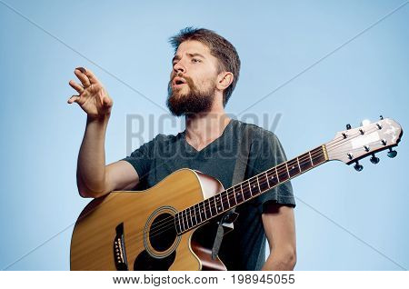 A man with a beard on a blue background holds a guitar, emotions, a musician.
