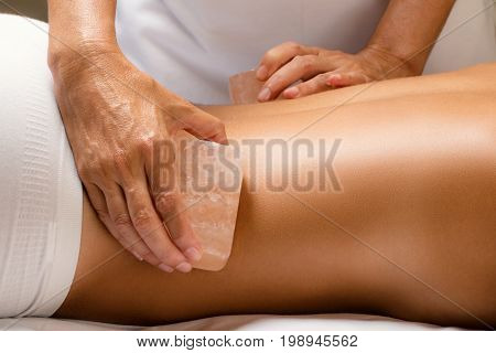Close up detail of himalayan salt stone massage. Therapist massaging lower back of woman with hot salt brick.