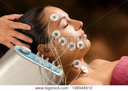 Close up portrait of woman having skin tightening treatment with low frequency electrodes. Hypo allergenic pads placed on woman's face.