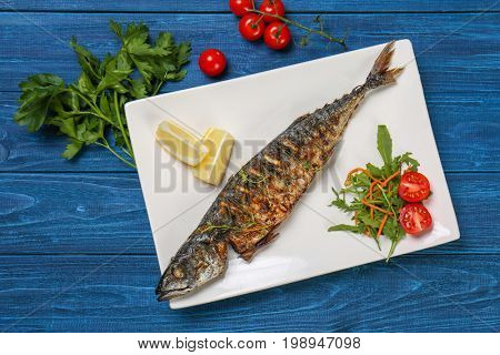 Grilled tasty fish on white plate with vegetables