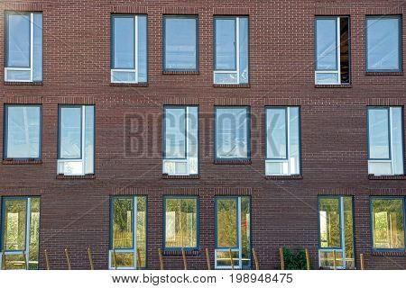 Many windows on a brown brick building wall