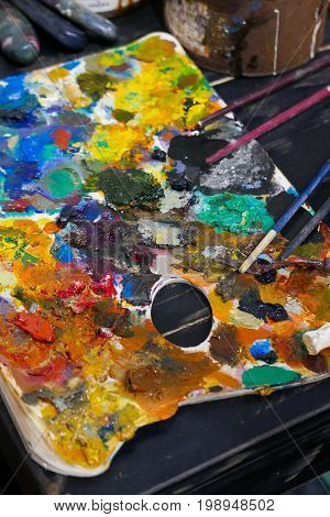 Artist work shop Abstract color Palette with brushes.