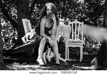 Young Woman In A Long Evening Dress Sits At A Table In The Woods. Black And White Photography