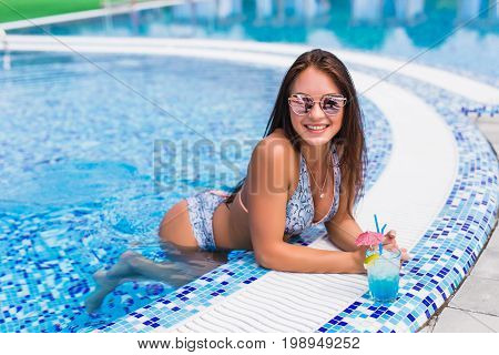 Seductive Girl In Blue Dress Relaxing At Swimming Pool Edge Poolside. Young Sexy Woman With Tropical
