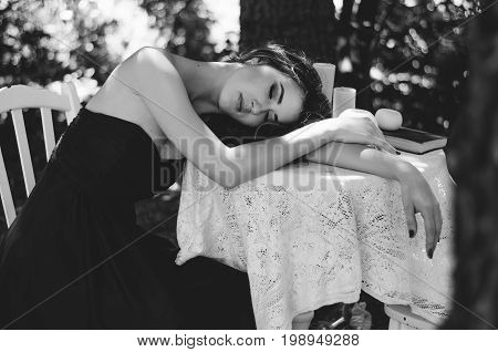 Portrait Of A Young Woman In A Long Evening Dress, She Sits At A Table In The Woods. Black And White