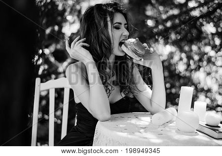 Young Girl In A Long Evening Dress Is Sitting At A White Table In The Park And Eating A Hamburger. B