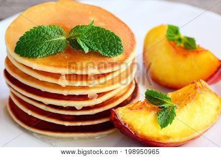 Easy pancakes with syrup and grilled fruit on a plate. Breakfast pancakes idea for children. Closeup