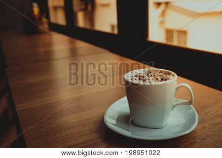 Capuccino coffee on wooden table the windows background