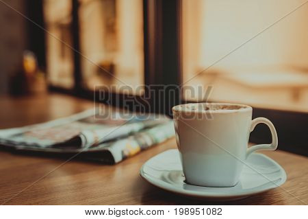Capuccino coffee and newspaper on wooden table the windows background