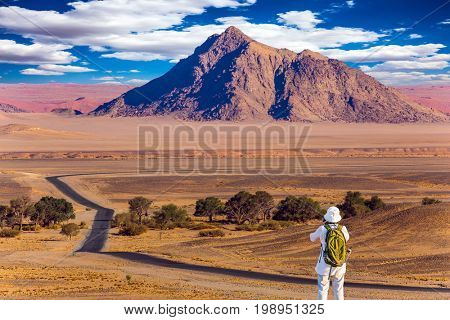 Purple and yellow mountains of the Namib desert. Sunset, Namibia. The concept of extreme and exotic tourism. Elderly woman with a green backpack is taking pictures of a landscape