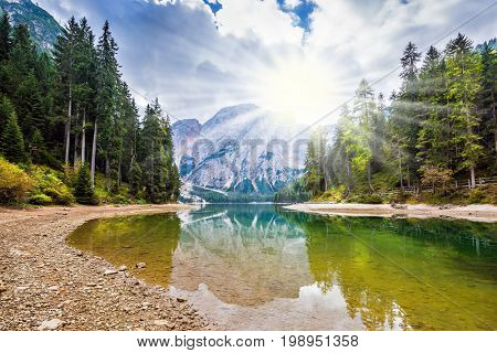 Magnificent lake in South Tyrol, Italy. The concept of walking and eco-tourism.  Sunshine on autumn day. Water reflects the surrounding mountains and forest