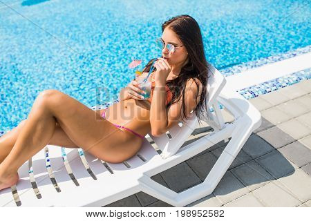 . Side View Of Beautiful Young Woman In White Bikini Drinking Cocktail And Smiling While Relaxing In