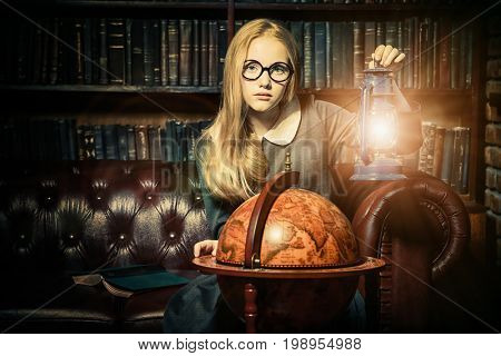 Smart student girl wearing black school dress and glasses is studying at the old library. Fairy vintage style. Education.