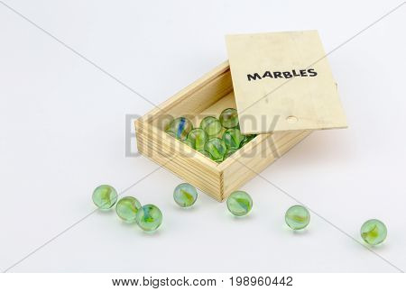 Wood box of green glass marbles on white background