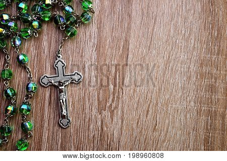 Christian rosary on a wooden texture background.