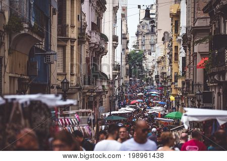The narrow street of Buenos Aires is crowded with people. The street is decorated with street umbrellas. The foreground is blurred.